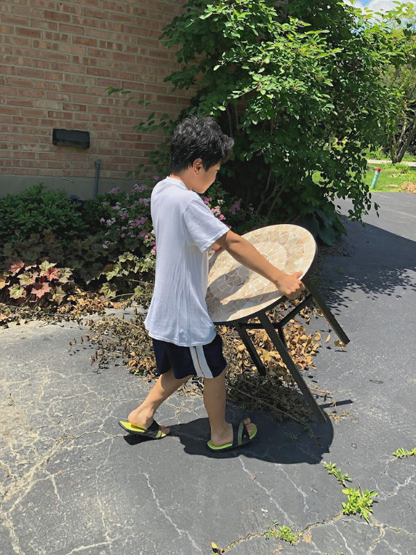 boy carrying a table