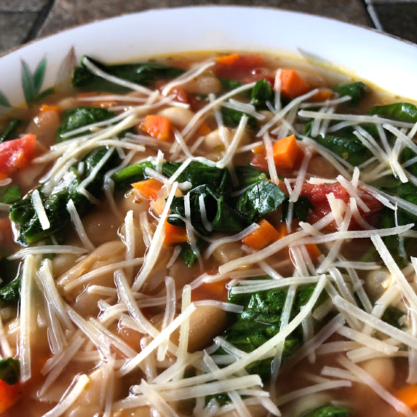 bowl of vegetarian white bean soup topped with Parmesan cheese