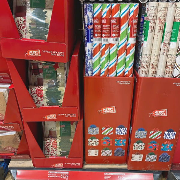 Merry Moments wrapping paper and holiday gift bags on the shelf at ALDI