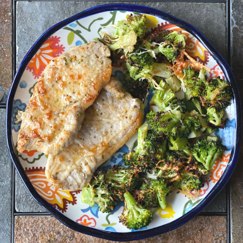 Plate of broiled Parmesan pork chops and broccoli in this week's ALDI meal plan