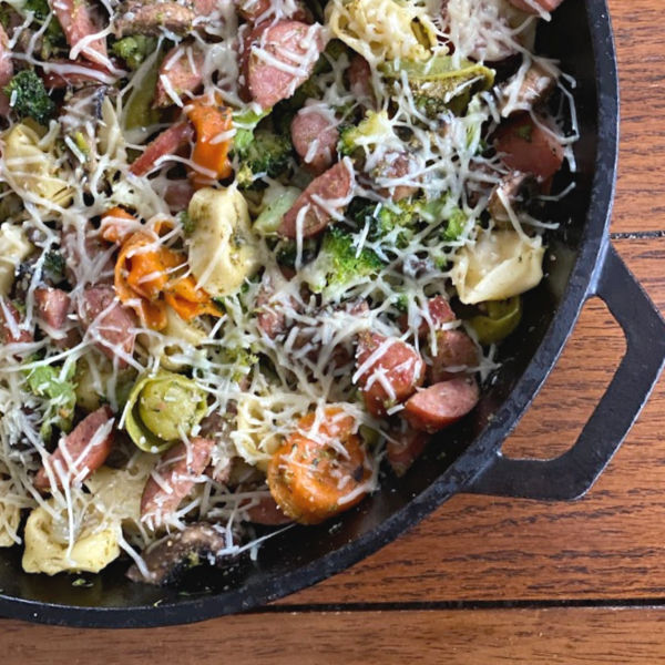 Smoked sausage & tortellini skillet topped with shredded Parmesan cheese